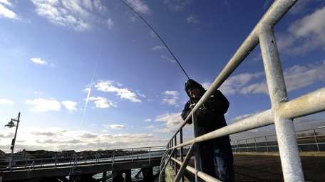Queens resident Angelo Savvidis fishes the the pier