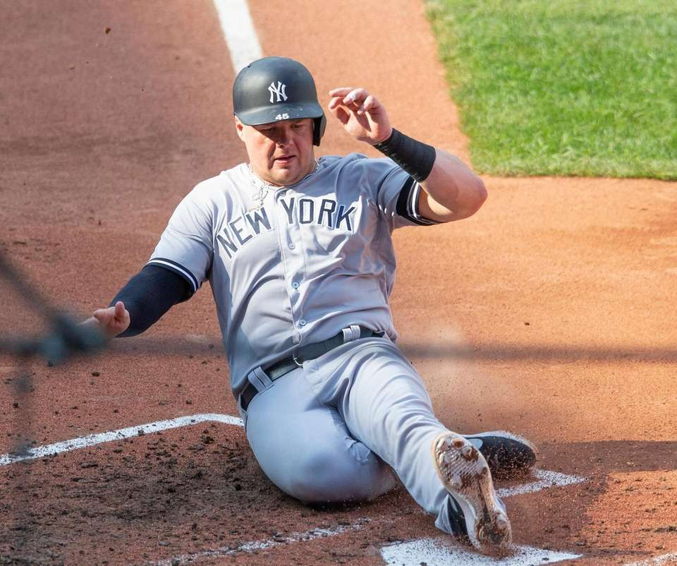 Yankees' Luke Voit slide into home plate during