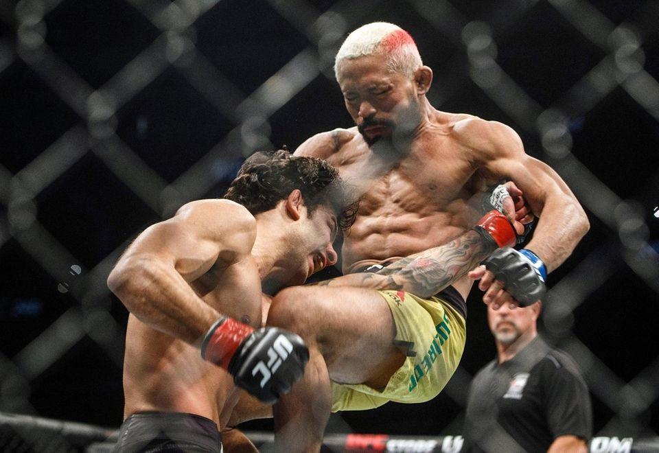 Alexandre Pantoja, left, is kneed by Deiveson Figueiredo