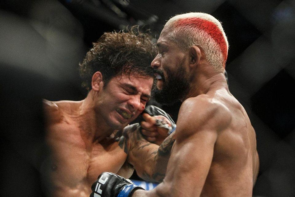 Alexandre Pantoja, left, is hit by Deiveson Figueiredo