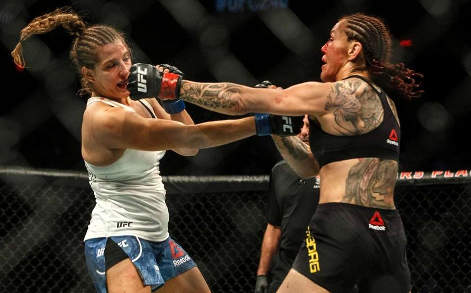 Cris Cyborg, right, hits Felicia Spencer during a