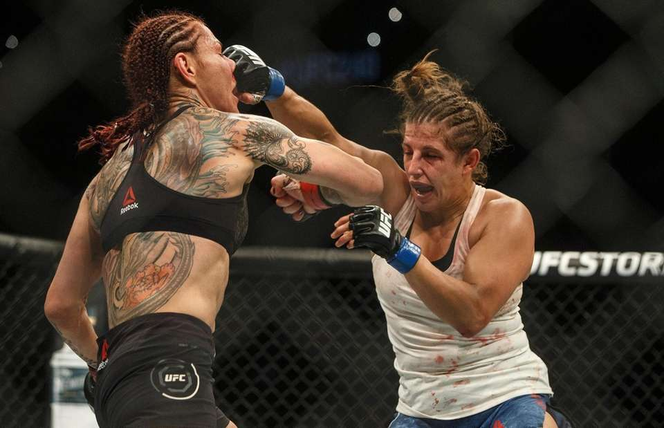 Cris Cyborg, left, is punched by Felicia Spencer