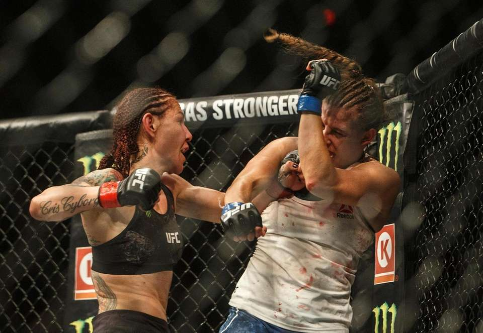 Cris Cyborg, left, hits Felicia Spencer during a