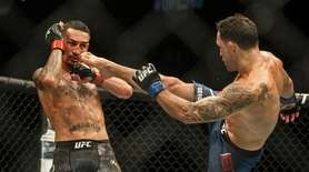 Max Holloway, left, blocks a kick from Frankie