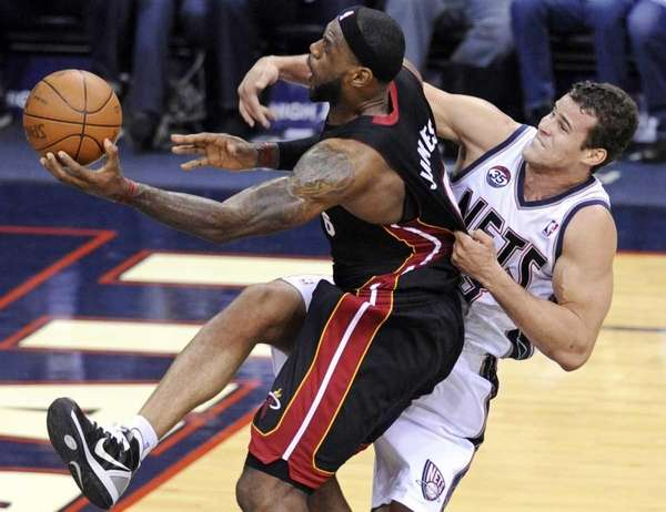 Miami Heat forward LeBron James, left, is fouled