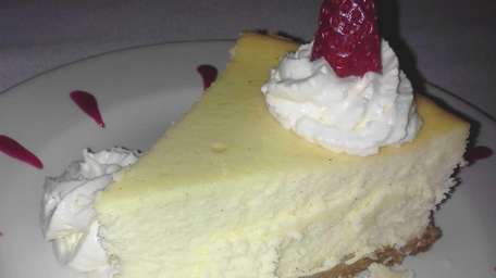 Cheesecake with whipped cream and strawberry topping served