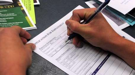 Teens fill out job applications as they look
