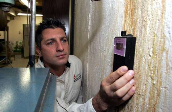 Richard Koller uses a moisture meter to inspect
