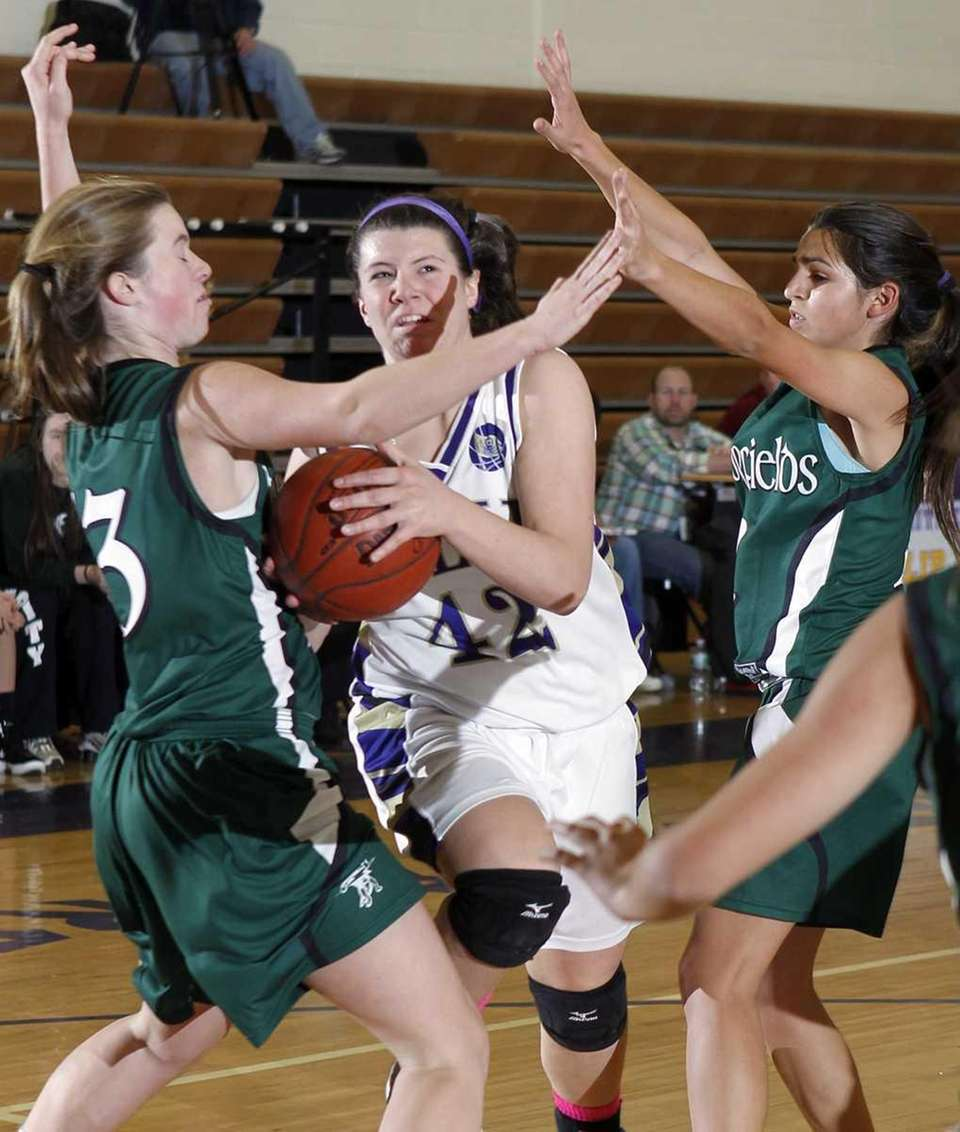 Islip's Shannon Duer drives between Harborfield's defenders Amy
