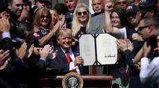 President Donald Trump shows off his signature on
