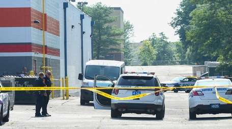 Police examine a delivery van behind an store