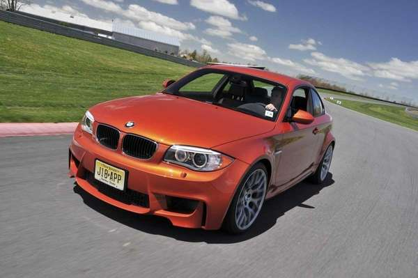 The 2011 BMW 1M coupe is driven on