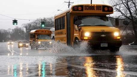 A school bus splashes through large puddle along