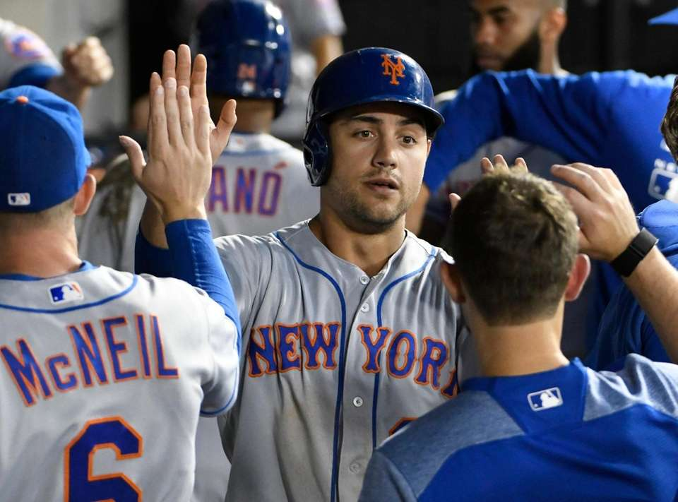 New York Mets' Michael Conforto, center, is greeted