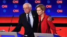 Sens. Bernie Sanders and Elizabeth Warren hug at