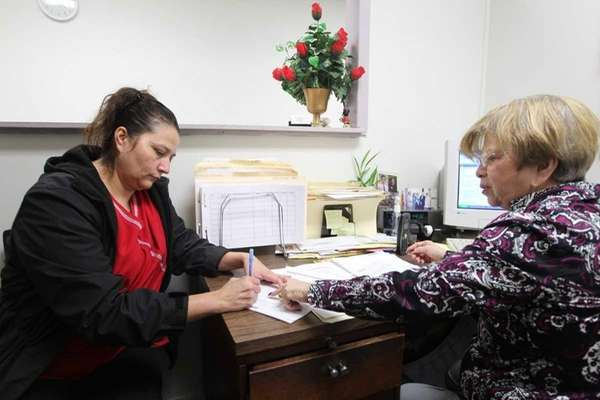 Sonia Escobar (left), of Roosevelt, receives help from