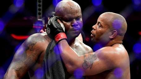 Daniel Cormier, right, talks with Derrick after defeating