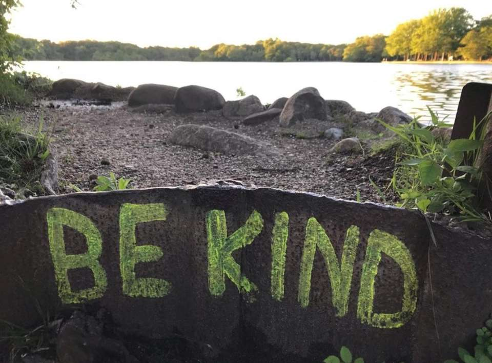 """Be Kind"" is painted along the walking trail"