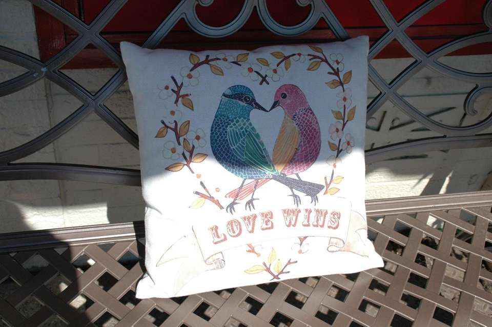 A pillow on a bench in front of