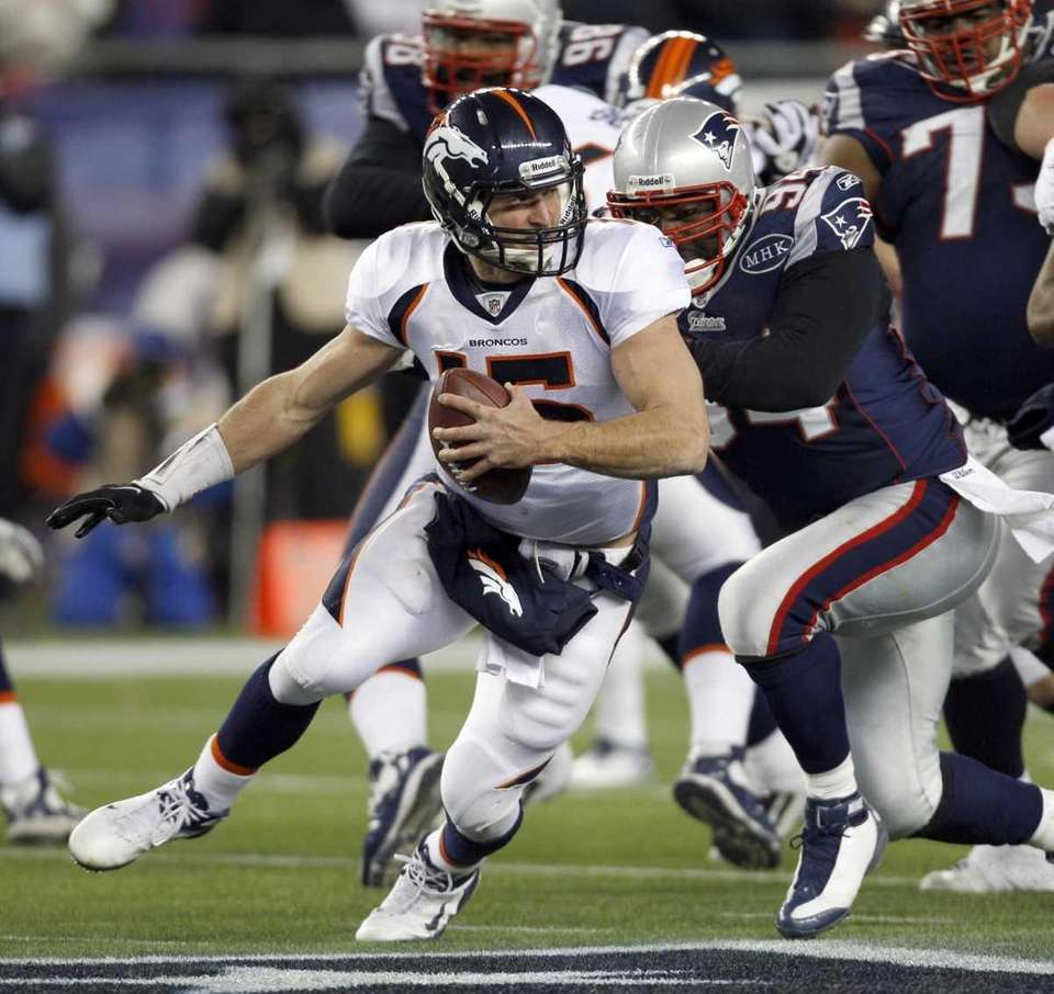 Denver Broncos quarterback Tim Tebow (15) scrambles to