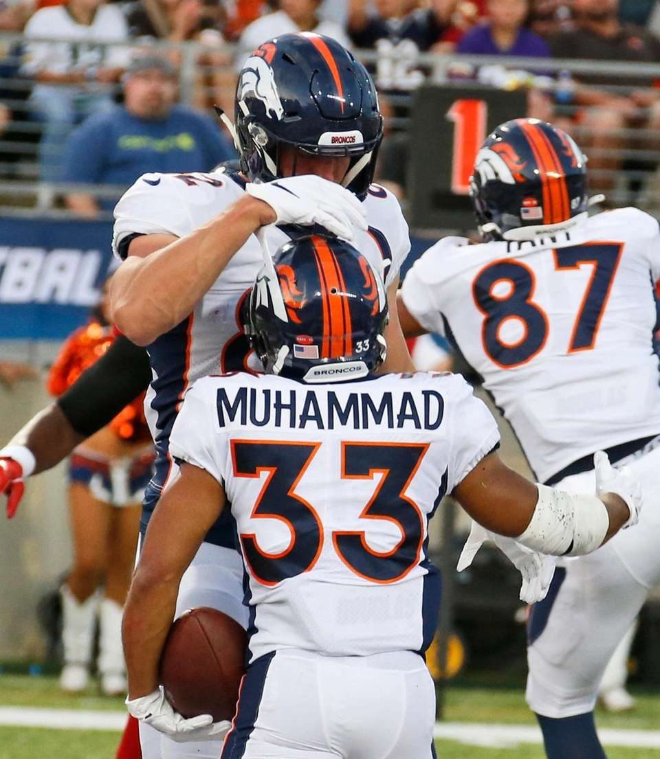 Denver Broncos fullback Andy Janovich, top, congratulates running