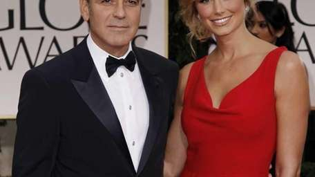 George Clooney, left, and Stacy Keibler arrive at