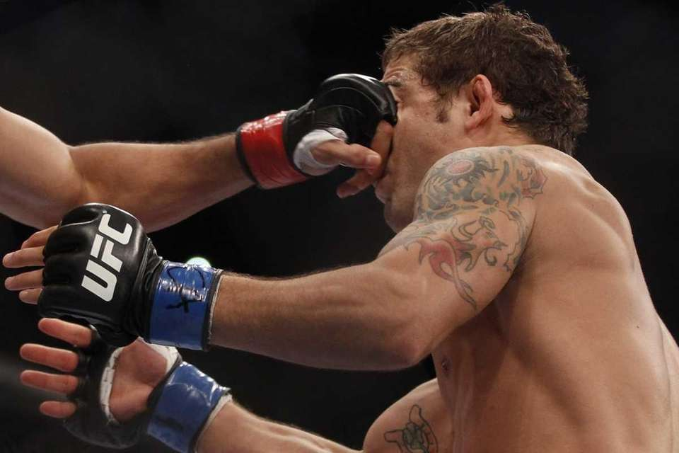 UFC featherweight champion Jose Aldo, left, punches Chad