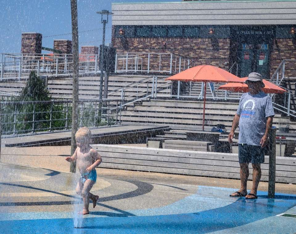Two-year-old Carmine Turchi running through the sprinkler with