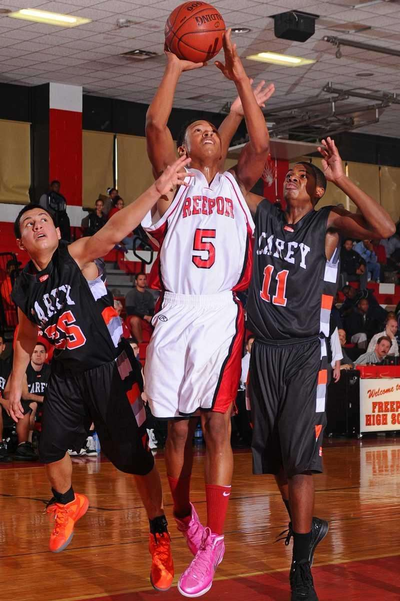 Jere Brown, center, attempts to drive past Carey