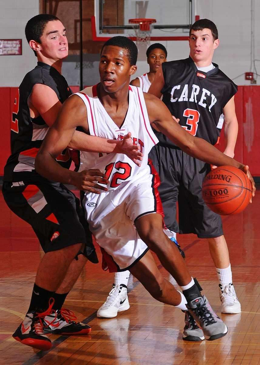 Isaiah Barnes, center, looks to drive past Carey