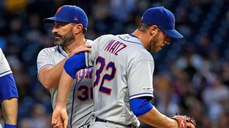 Mets manager Mickey Callaway, left, takes the ball