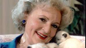 Actress Betty White holds some Siamese kittens at