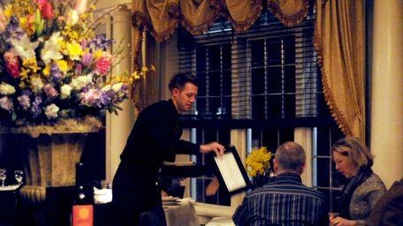 A server brings menus to diners at Blackwells