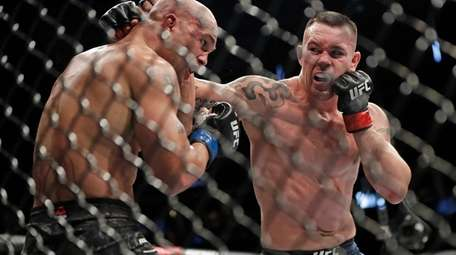 Colby Covington, right, punches Robbie Lawler during the