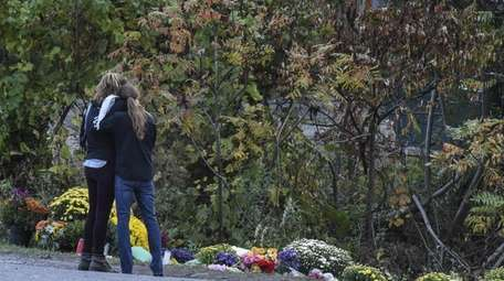 People mourn on Oct. 8, 2018, at the