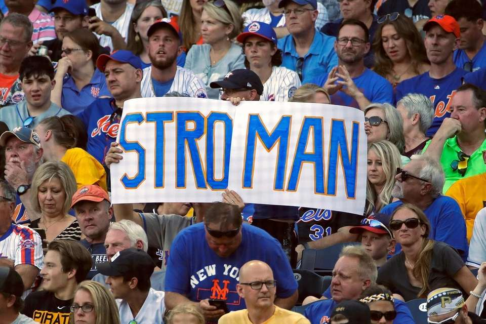 New York Mets fans hold a sign behind