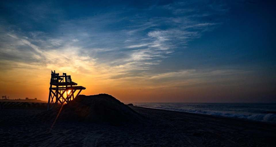 The sun rises over the lifeguard stand at