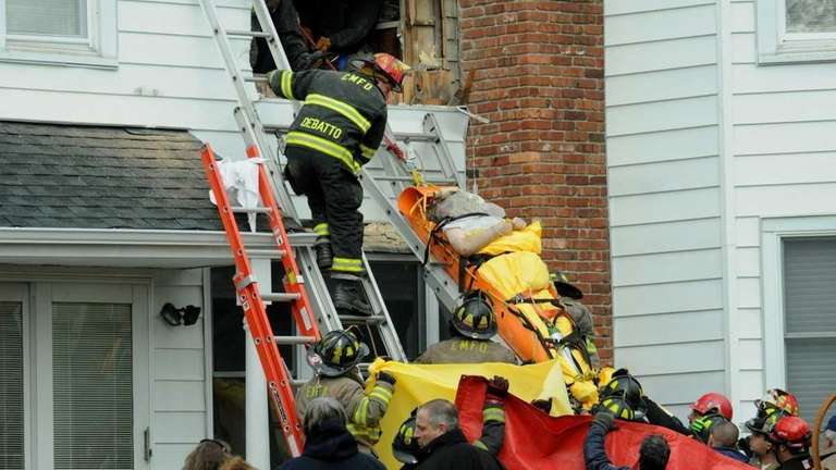 Firefighters remove a man from the second floor