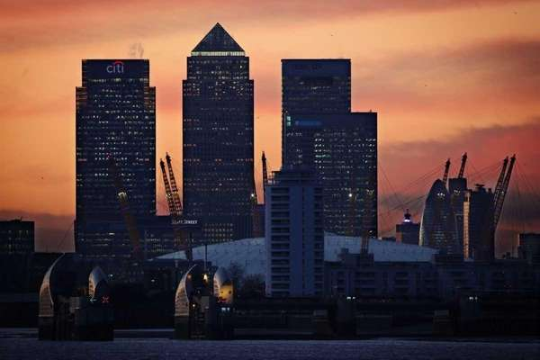 The sun sets behind The London Skyline, featuring