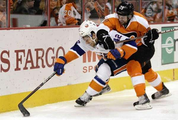 Dylan Reese, left, is pressured by Philadelphia Flyers'