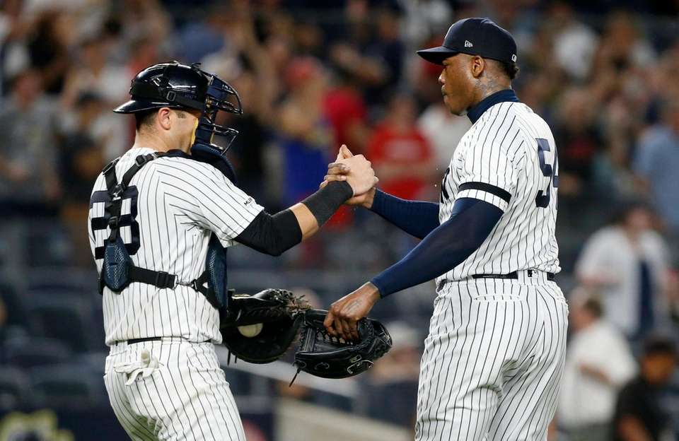 Aroldis Chapman #54 and Austin Romine #28 of