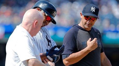 New York Yankees' Edwin Encarnacion is helped by