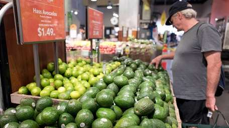 A man shops for avocados at a Whole