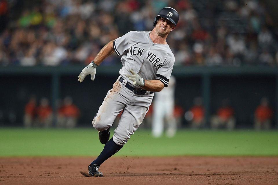 The Yankees' Brett Gardner runs to third on