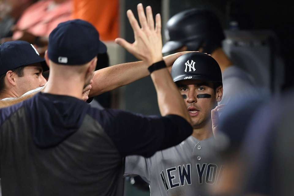 The Yankees' Mike Tauchman is congratulated after scoring