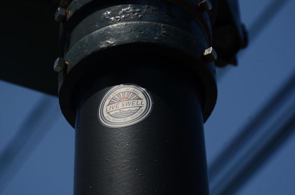 """""""Live Swell"""" sticker sits on a telephone pole"""