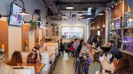 Patrons dine in wooden booth seating and at