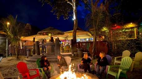 Guests sit by the outdoor fire pit at