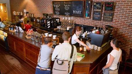 Barista makes coffee drinks behind the counter of