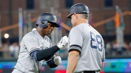 Yankees shortstop Didi Gregorius is congratulated by third